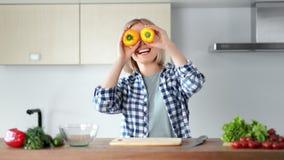 Retrato da dança feliz da mulher que tem o divertimento com pimentas amarelas na cozinha dos olhos em casa filme