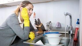 Retrato da dona de casa cansado da virada nas luvas que olham pratos sujos no dissipador e na água de fluxo fotos de stock royalty free
