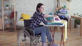 Retrato da dona de casa deficiente da jovem mulher que faz trabalhos de casa
