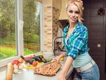 Retrato da dona de casa loura de sorriso lindo que mostra a pizza recentemente cozinhada do corte na tábua de pão fotografia de stock royalty free
