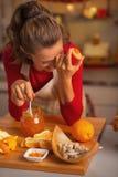 Retrato da dona de casa que ri ao comer o doce alaranjado na cozinha fotos de stock royalty free