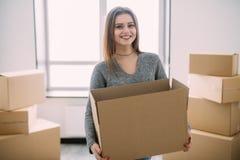 Retrato da embalagem moreno nova bonita que leva algumas caixas para mover-se em sua casa nova imagem de stock