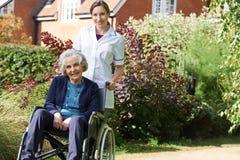 Retrato da equipa de tratamento que empurra a mulher superior na cadeira de rodas Fotos de Stock