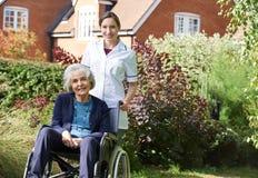 Retrato da equipa de tratamento que empurra a mulher superior na cadeira de rodas imagens de stock royalty free