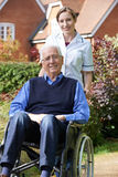 Retrato da equipa de tratamento que empurra o homem superior na cadeira de rodas imagem de stock royalty free