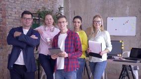 Retrato da equipe criativa no escritório moderno, de meninos felizes do negócio e de meninas durante horários laborais no escritó