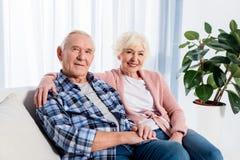 retrato da esposa e do marido superiores de sorriso que olham a câmera ao descansar no sofá imagem de stock