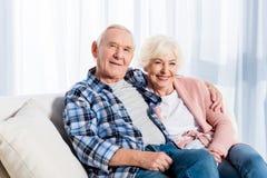 retrato da esposa e do marido superiores de sorriso que olham a câmera ao descansar no sofá imagens de stock royalty free