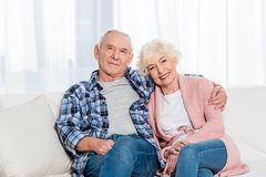 retrato da esposa e do marido superiores de sorriso que olham a câmera ao descansar no sofá foto de stock