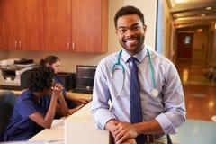Retrato da estação do doutor At Nurse masculino no hospital foto de stock