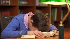 Retrato da estudante que faz seus trabalhos de casa e que dorme no livro vídeos de arquivo