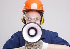Retrato da fêmea caucasiano expressivo com a gritaria do chifre do altifalante no capacete de segurança Imagem de Stock Royalty Free