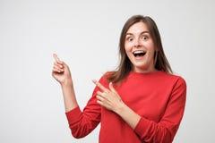 Retrato da fêmea caucasiano nova no t-shirt vermelho que mostra algo interessante na parede do espaço da cópia para a informação imagem de stock
