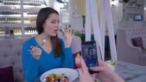 Retrato da fêmea do vegetariano com o alimento útil fotografado no smartphone para redes sociais durante o jantar saudável vídeos de arquivo