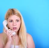 Retrato da fêmea nova em choque ao falar no telefone que tem foto de stock royalty free