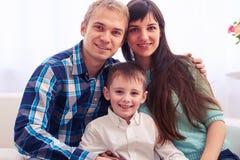 Retrato da família adorável nova com criança em casa Fotografia de Stock