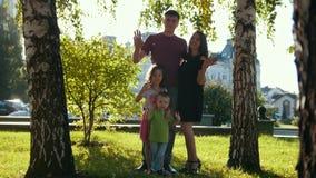Retrato da família completa em um parque na noite do verão - pai, mamãe, filha e rapaz pequeno - mãos de ondulação vídeos de arquivo