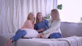 Retrato da família de amor, meninas de sorriso felizes com a mamã amado que abraça ao sentar-se na cama