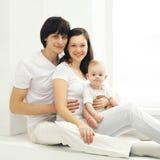 Retrato da família de pais e do bebê felizes em casa na sala branca Fotos de Stock Royalty Free
