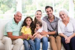 Retrato da família de sorriso com bebê ao sentar-se no sofá Fotografia de Stock