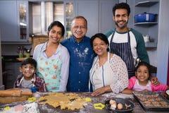 Retrato da família de sorriso da multi-geração que está junto na cozinha fotos de stock royalty free
