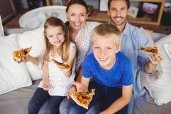 Retrato da família de sorriso que guarda fatias da pizza ao sentar-se no sofá Imagem de Stock