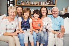 Retrato da família de sorriso que senta-se no sofá Fotografia de Stock Royalty Free