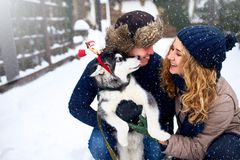 Retrato da família dos pares felizes bonitos que abraçam com seu cão do malamute do Alasca que lambe a cara do homem Vestir engra foto de stock royalty free