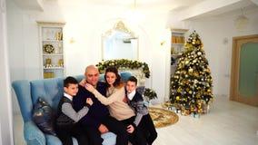 Retrato da família encantador e exemplar, pais de inquietação e crianças que se sentam no sofá azul na sala decorada festiva vídeos de arquivo