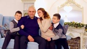 Retrato da família exemplar, pais loving e filhos que se sentam no sofá azul na sala decorada festiva com árvore de Natal filme