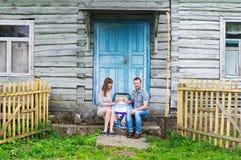 Retrato da família feliz nova com a criança do bebê no transporte de bebê que senta-se junto na frente da casa de madeira retro v foto de stock