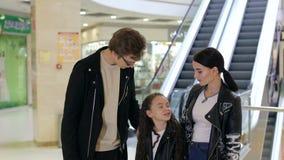 Retrato da família feliz nova no shopping com pacotes da compra filme