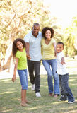 Retrato da família feliz que anda no parque Imagens de Stock Royalty Free