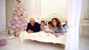 Retrato da família feliz que comunica e levanta in camera o encontro na cama no quarto brilhante com árvore de Natal e filme