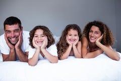 Retrato da família feliz que encontra-se na cama foto de stock