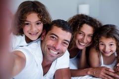 Retrato da família feliz que encontra-se na cama fotos de stock