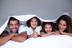 Retrato da família feliz que encontra-se sob um bedsheet imagem de stock royalty free