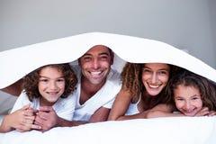 Retrato da família feliz que encontra-se sob um bedsheet foto de stock royalty free