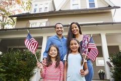 Retrato da família fora da casa que guarda bandeiras americanas fotos de stock royalty free