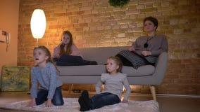 Retrato da família da mãe caucasiano com as três filhas que sentam-se no sofá e no filme de observação na atmosfera de casa calma filme