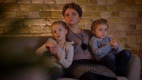 Retrato da família da mãe caucasiano que abraça suas duas filhas e que olha o filme na atmosfera de casa confortável vídeos de arquivo