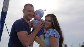 Retrato da família na luz solar, beijo parental para o bebê, casal novo do bom humor com o filho no ar livre, vídeos de arquivo