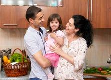 Retrato da família no interior da cozinha com frutas e legumes frescas, a menina saudável do conceito do alimento, da mulher grav foto de stock