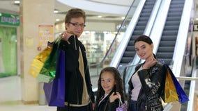 Retrato da família nova no shopping com pacotes da compra perto da escada rolante filme
