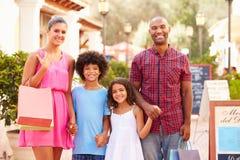 Retrato da família que anda ao longo da rua com sacos de compras fotografia de stock royalty free