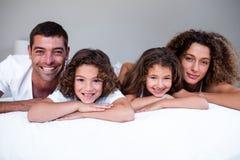 Retrato da família que encontra-se na cama foto de stock royalty free
