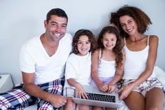 Retrato da família que usa o portátil junto na cama fotos de stock royalty free