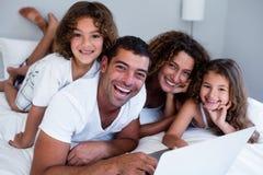 Retrato da família que usa o portátil junto na cama imagens de stock