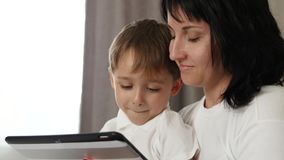 Retrato da fam?lia Mãe e criança que olham a tela de um tablet pc com emoções: alegria, felicidade, divertimento video estoque