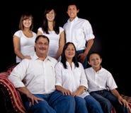 Retrato da família assentado sobre com fundo preto Imagens de Stock Royalty Free